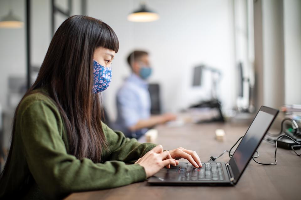 Young woman wearing face mask working on her laptop in office. Woman sitting at her desk wearing a protective mask to prevent from infectious diseases.