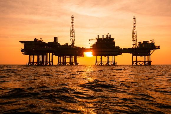 An offshore oil rig in silhouette against a sunset