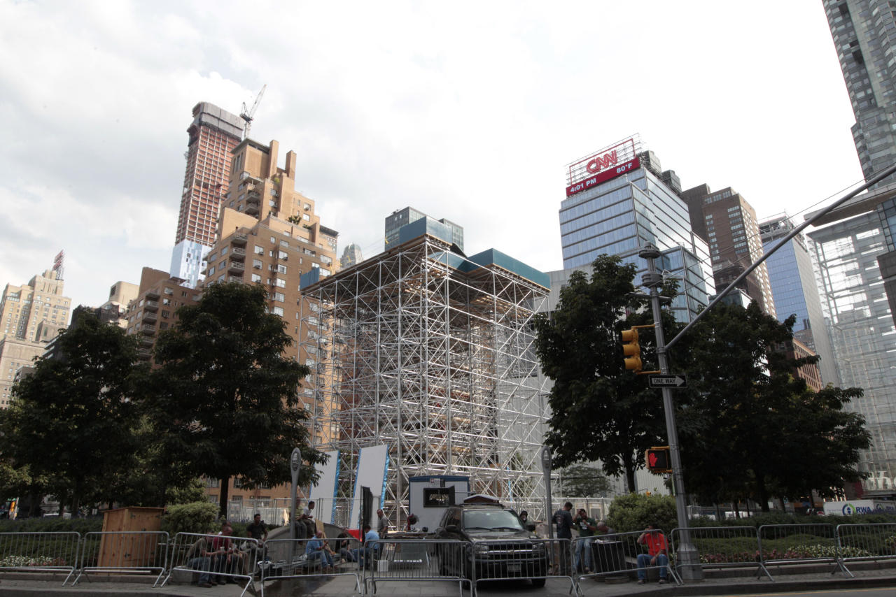 "Scaffolding surrounds the statue of Christopher Columbus, Tuesday, Aug. 21, 2012 in New York's Columbus circle. Japanese artist Tatzu Nishi is constructing ""Discovering Columbus,"" a contemporary living room around a statue of Columbus as a way to intimately engage the public with the iconic figure which looms six stories above a busy intersection of mid-Manhattan. But some Italian-Americans say the art project makes a mockery of the great explorer and trivializes history. (AP Photo/Mary Altaffer)"