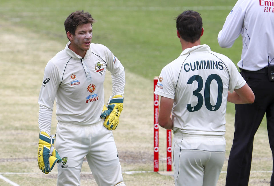 Australian captain Tim Paine, left, talks with bowler Pat Cummins during play on day three of the fourth cricket test between India and Australia at the Gabba, Brisbane, Australia, Sunday, Jan. 17, 2021. (AP Photo/Tertius Pickard)