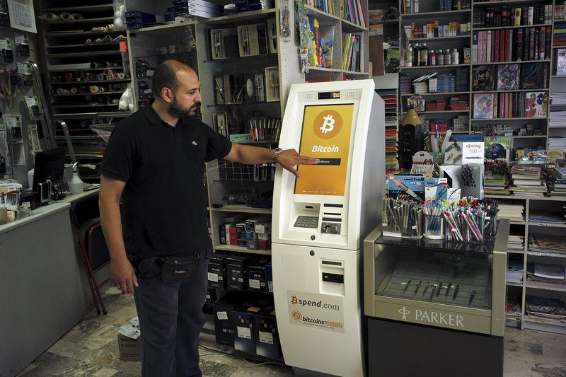 A man demonstrates the use of a Bitcoin ATM at a bookstore in Acharnai in northern Athens, Greece
