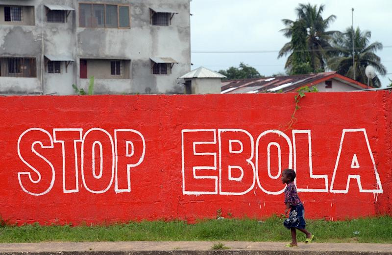 "A girl walks past a slogan painted on a wall reading ""Stop Ebola"" in Monrovia on August 31, 2014 (AFP Photo/Dominique Faget)"
