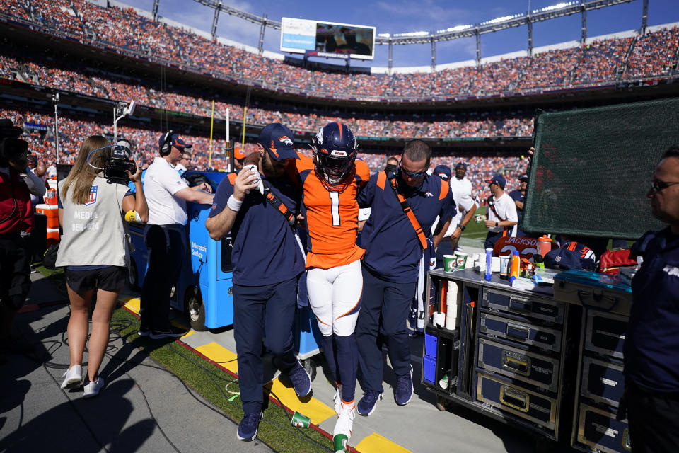 Denver Broncos wide receiver K.J. Hamler if helped off the field after an injury against the New York Jets during the first half of an NFL football game, Sunday, Sept. 26, 2021, in Denver. (AP Photo/Jack Dempsey)