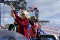 Supporters of President Donald Trump wave as the motorcade passes ny on the road to Mar-a-Lago, Trump's Palm Beach estate, on Wednesday, Jan. 20, 2021, in West Palm Beach, Fla. (AP Photo/Lynne Sladky)