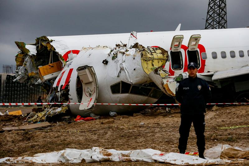 Turkish police guard the wreckage of a plane operated by Pegasus Airlines after it skidded off the runway: AP