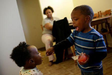 Victoria Marshall watches as her two-year-old son Ed Brown Jr. who has lead poisoning feed his one-year-old sister Jewel Brown at their home in South Bend, Indiana, November 29, 2016. REUTERS/Joshua Lott