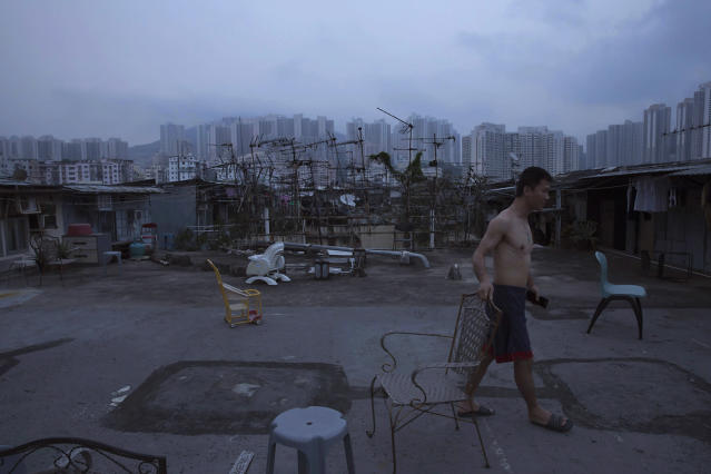 <p>A resident walks outside his illegal rooftop hut, located next to a public housing estate, against the backdrop. of the Hong Kong skyline, May 6, 2017. (Photo: Kin Cheung/AP) </p>