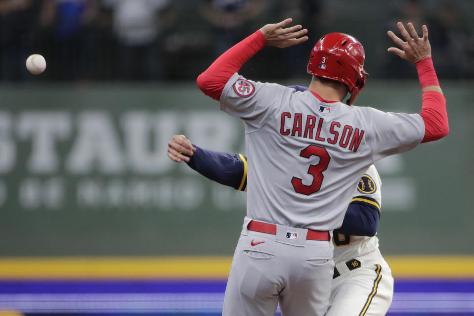 Milwaukee Brewers' Kolten Wong throws around St. Louis Cardinals' Dylan Carlson (3) during the first inning of a baseball game Tuesday, May 11, 2021, in Milwaukee. Carlson was safe at second base, and Paul Goldschmidt was out at first. (AP Photo/Aaron Gash)