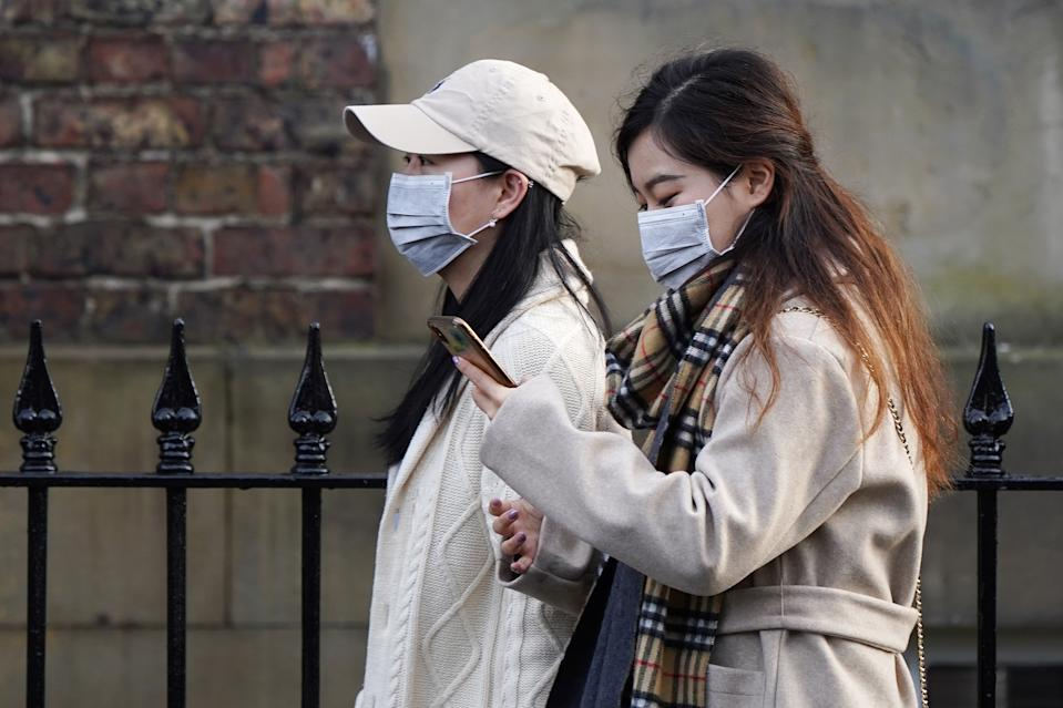 Two women wearing face masks walk through the city centre near to the Royal Victoria Infirmary where two patients who have tested positive for the Wuhan coronavirus are being treated by specialist medical workers on January 31, 2020 in Newcastle upon Tyne, England. (Getty Images)