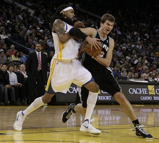 San Antonio Spurs center Tiago Splitter (22), from Brazil, right, tries to control the ball next to Golden State Warriors center Mikki Moore (31) during the third quarter of an NBA basketball game in Oakland, Calif., Monday, April 16, 2012. (AP Photo/Jeff Chiu)