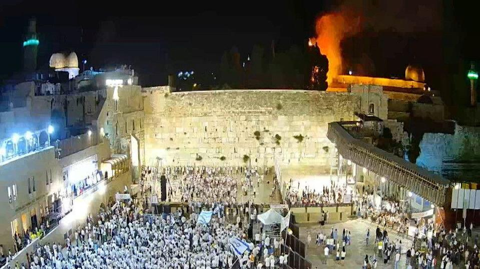 Israelis gather at the Western Wall as a blaze is seen in the background at the compound that houses al-Aqsa mosque in Jerusalem's Old City, May 10, 2021. © Reuters / Reuters TV (Photo: reuters)