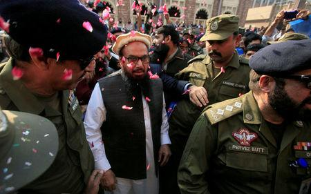 FILE PHOTO: Hafiz Saeed is showered with flower petals as he walks to court before a Pakistani court ordered his release from house arrest in Lahore, Pakistan November 22, 2017. REUTERS/Mohsin Raza/File Photo