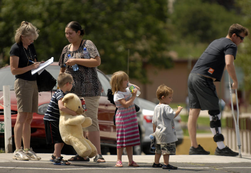 Evacuees of the Waldo Canyon Fire are assisted by a volunteers from the Red Cross at the Cheyenne Mountain High School evacuation center on Wednesday, June 27, 2012, in Colorado Springs, Colo. The wildfire doubled in size overnight to about 24 square miles (62 square kilometers), and has so far forced mandatory evacuations for more than 32,000 residents. (AP Photo/Bryan Oller)