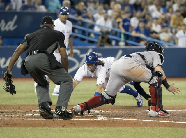 Boston Red Sox catcher Christian Vazquez can't get the tag on Toronto Blue Jays' Bo Bichette as he scores on a double by Vladimir Guerrero Jr. during the fifth inning of a baseball game, Wednesday, Sept. 11, 2019 in Toronto. (Fred Thornhill/The Canadian Press via AP)