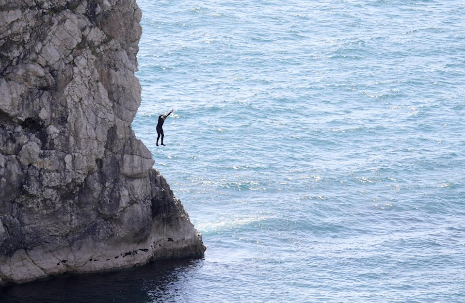 A person jumps into the sea from Durdle Door, near Lulworth, despite Dorset Council announcing that the beach was closed to the public after three people were seriously injured jumping off cliffs into the sea.
