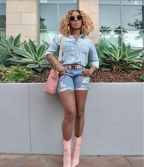 Mary J. Blige standing against a wall with plants behind her