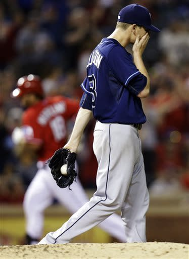 Tampa Bay Rays starting pitcher Jeremy Hellickson, right, reacts as Texas Rangers' Mitch Moreland rounds the bases after hitting a solo home run during the fourth inning of a baseball game, Monday, April 8, 2013, in Arlington, Texas. (AP Photo/LM Otero)