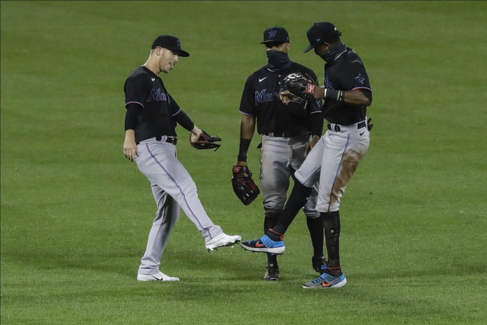 Miami Marlins Corey Dickerson, left, Magneuris Sierra, center, and Matt Joyce, right, celebrate after a baseball game against the New York Mets Friday, Aug. 7, 2020, in New York. The Marlins won 4-3. (AP Photo/Frank Franklin II)