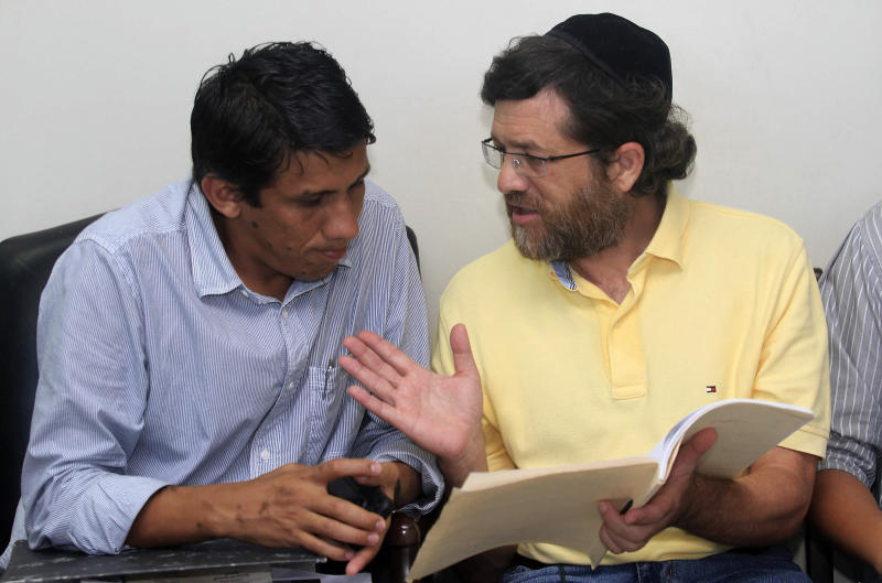 FILE - In this March 21, 2012 file photo, U.S. businessman Jacob Ostreicher, right, talks to his attorney Abel Montano at a local courthouse in Santa Cruz, Bolivia. In an unlikely tale, the Orthodox Jew from New York City came to Bolivia to rescue a rice-growing venture, was thrown in jail on suspicion of money laundering and, with the aid of actor Sean Penn, winds up triggering one of the biggest scandals of Evo Morales' presidency. The saga came to light 18 months ago when Ostreicher was arrested while trying to salvage a multimillion-dollar investment he was managing for Swiss partners. After Penn directly interceded on Ostreicher's behalf, it could now be reaching its end game. (AP Photo/File)
