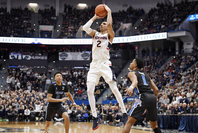 Connecticut's James Bouknight, center, shoots between Memphis' Boogie Ellis, left, and Tyler Harris, right, in the second half of an NCAA college basketball game, Sunday, Feb. 16, 2020, in Hartford, Conn. (AP Photo/Jessica Hill)