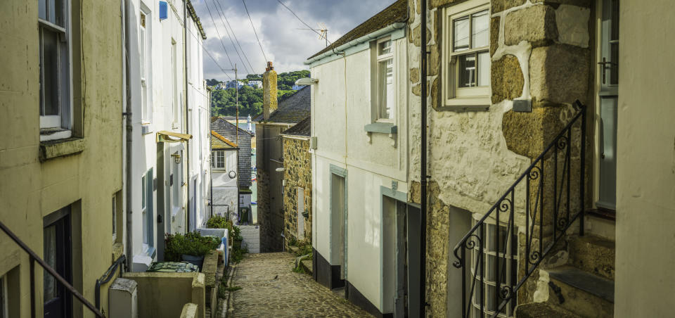 The narrow cobbled streets of St Ives are lined with honey hued houses. (Getty Images)