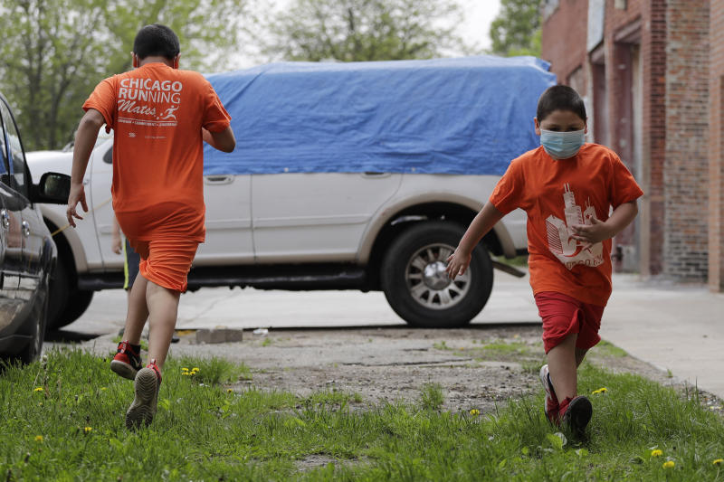 Mariano Ochoa, 9, left, and his brother Jesus Ochoa, 5, run in front of their home in Chicago, Friday, May 22, 2020. Mariana Ochoa has three young boys, ages 9, 7, and 5, and Chicago Run's at-home fitness programs have become an essential part of the family's routine during the coronavirus pandemic. (AP Photo/Nam Y. Huh)