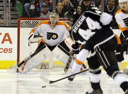 Philadelphia Flyers goalie Steve Mason (35) waits as Los Angeles KIngs defenseman Robyn Regehr (44) shoots in the first period of an NHL hockey game in Los Angeles Saturday, Feb. 1, 2014. (AP Photo/Reed Saxon)