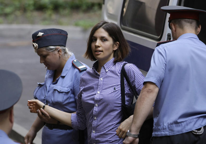 "Nadezhda Tolokonnikova, center, a member of feminist punk group Pussy Riot is escorted to a court room in Moscow, Russia, Monday, July 30, 2012. Three members of the band are facing trial for performing a ""punk prayer"" against Vladimir Putin from a pulpit of Moscow's main cathedral before Russia's presidential election in March, in which he won a third term. (AP Photo/Mikhail Metzel)"