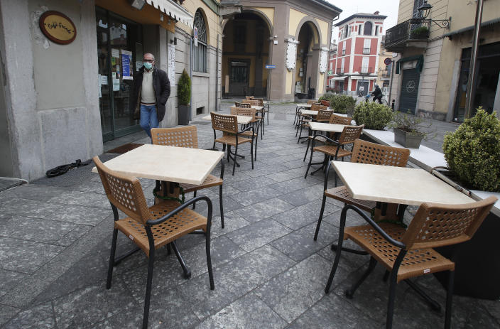 In this photo taken on Thursday, March 12, 2020, a man wearing a mask walks in Codogno, Italy. The northern Italian town that recorded Italy's first coronavirus infection has offered a virtuous example to fellow Italians, now facing an unprecedented nationwide lockdown, that by staying home, trends can reverse. Infections of the new virus have not stopped in Codogno, which still has registered the most of any of the 10 Lombardy towns Italy's original red zone, but they have slowed. For most people, the new coronavirus causes only mild or moderate symptoms. For some it can cause more severe illness. (AP Photo/Antonio Calanni)