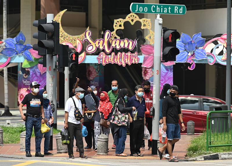 People wearing face masks amid the COVID-19 outbreak wait at a road crossing with building displays of festive decorations at the Geylang Serai market here on 21 May, 2020. (PHOTO: AFP via Getty Images)