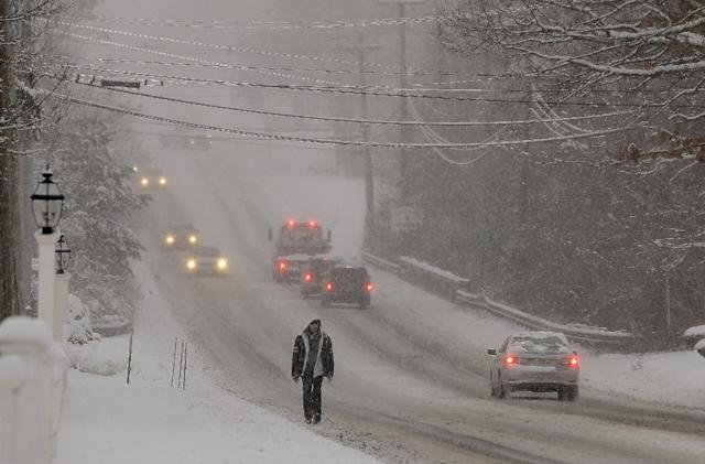 Traffic is sparse and the sidewalks impassable as a heavy snow falls in Pembroke, Mass., Wednesday morning, Feb. 5, 2014. The storm is expected to drop a foot or more of snow on some areas of Massachusetts Wednesday making driving treacherous. (AP Photo/Stephan Savoia)
