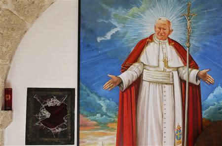 A broken glass of a niche where the reliquary with the blood of the late Pope John Paul II was located is seen next to a painting of the late Pope in the small mountain church of San Pietro della Ienca