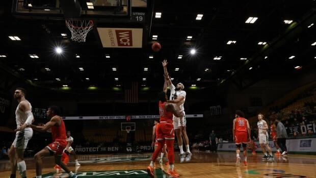 Fardaws Aimaq, pictured here reaching for the ball, has been named the Western Athletic Conference Men's Basketball Player of the Year and Defensive Player of the Year. (Jay Drowns/UVU Marketing - image credit)