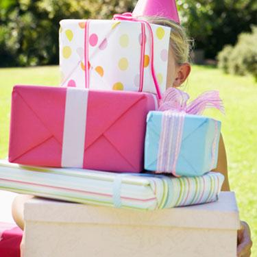 Young-girl-holding-large-stack-of-birthday-gifts_web