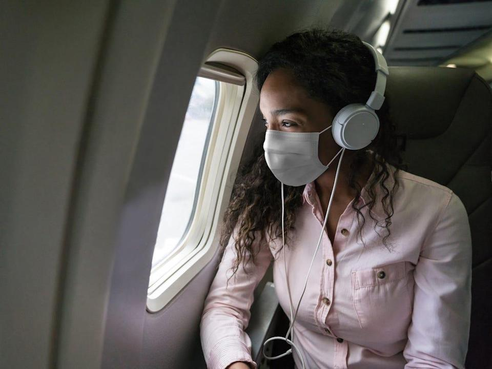 Woman listening to music while flying on an airplane wearing a facemask - stock photo