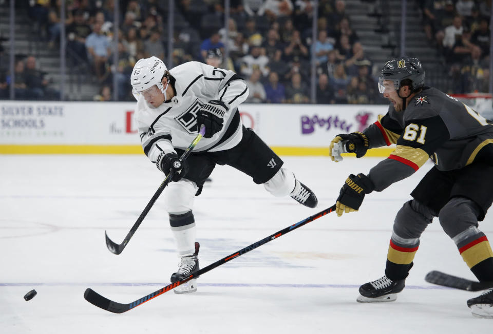 Los Angeles Kings right wing Tyler Toffoli (73) hits the puck upice against Vegas Golden Knights right wing Mark Stone during the first period of an NHL preseason hockey game Friday, Sept. 27, 2019, in Las Vegas. (AP Photo/John Locher)