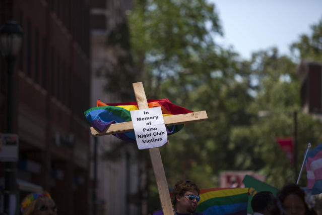 <p>Austin Ellis, a member of Metropolitan Community Church, carries a cross with a sign in memory of the victims of the Pulse nightclub shooting as he marches in the 2016 Gay Pride Parade on June 12, 2016 in Philadelphia, Pennsylvania. (Jessica Kourkounis/Getty Images) </p>