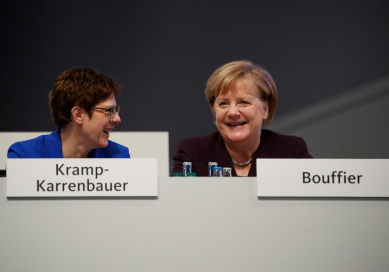 Leader of the Christian Democratic Union (CDU) with Annegret Kramp-Karrenbauer (L) with her mentor German Chancellor Angela Merkel react during the congress of Germany's conservative Christian Democratic Union (CDU) party