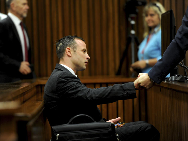 Oscar Pistorius sits in the dock as he waits for proceedings to begin at a court in Pretoria, South Africa, Tuesday, March 18, 2014. Pistorius is on trial for the murder of his girlfriend Reeva Steenkamp on Valentines Day, 2013. (AP Photo/Werner Beukes, Pool)