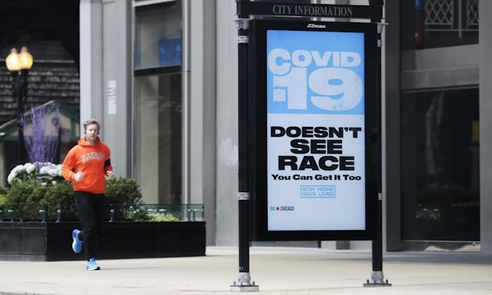 A sign warning residents of coronavirus is seen on the sidewalk in downtown Chicago.