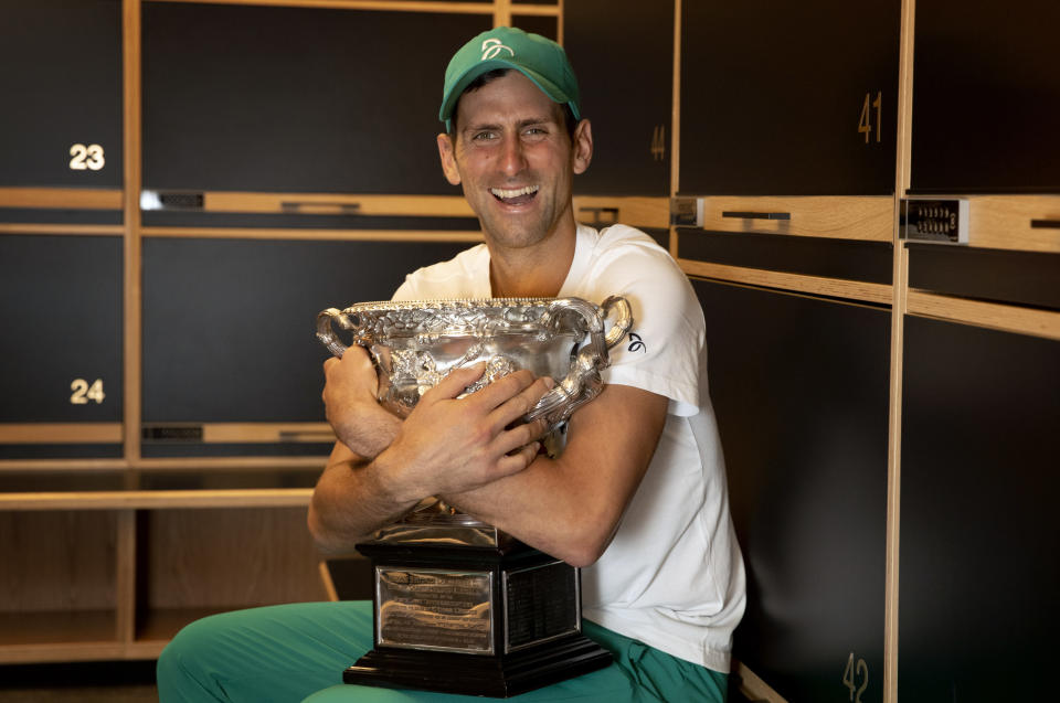 Serbia's Novak Djokovic embraces the Norman Brooks Challenge Cup in the locker room after defeating Russia's Daniil Medvedev in the men's singles final at the Australian Open tennis championship in Melbourne, Australia, Sunday, Feb. 21, 2021.(Fiona Hamilton/Tennis Australia via AP)