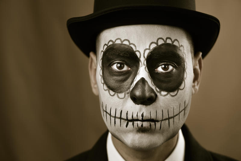 portrait of a man with calaveras makeup, wearing jacket and top hat, against a brown background