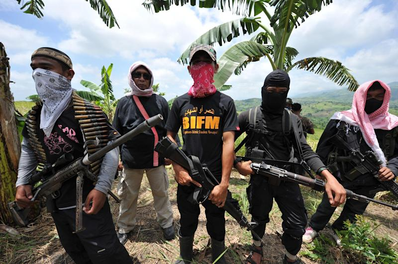 Members of the breakaway Muslim separatist group Bangsamoro Islamic Freedom Fighters (BIFF) stand guard during a clandestine press conference in the town of Datu Unsay, sothern Maguindanao province in the Philippines, on August 28, 2011 (AFP Photo/Ted Aljibe)