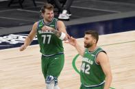 Dallas Mavericks' Luka Doncic (77) and Maxi Kleber (42) celebrate a 3-point basket scored by Doncic during the first half of an NBA basketball game against the New Orleans Pelicans in Dallas, Wednesday, May 12, 2021. (AP Photo/Tony Gutierrez)