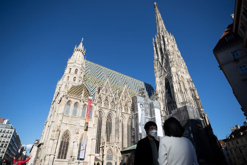 A tourist wears a protective mask in front of St. Stephen's Cathedral in Vienna