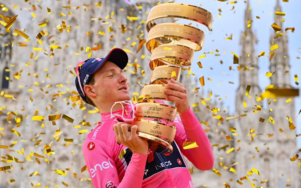 Tao Geoghegan Hart poses with the trophy in front of the gothic cathedral after winning the Giro d'Italia cycling race, in Milan, Italy, Sunday, Oct. 25, 2020 - AP/Gian Mattia D'Alberto