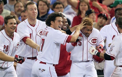 Cincinnati Reds' Wilson Valdez (15) is mobbed by his teammates after driving in the winning run with a bunt in the 10th inning of a baseball game against the Detroit Tigers, Friday, June 8, 2012, in Cincinnati. Cincinnati won 6-5. (AP Photo/Al Behrman)