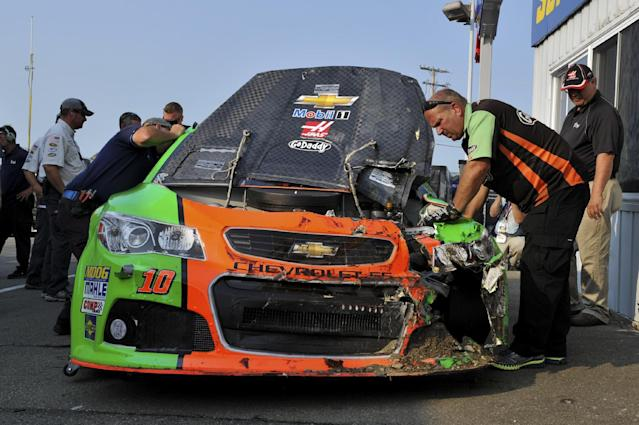 Crew members look over Danica Patrick's car after she crashed during a practice session for Sunday's NASCAR Sprint Cup series auto race at Watkins Glen International, Friday, Aug. 8, 2014, in Watkins Glen N.Y. (AP Photo/Derik Hamilton)