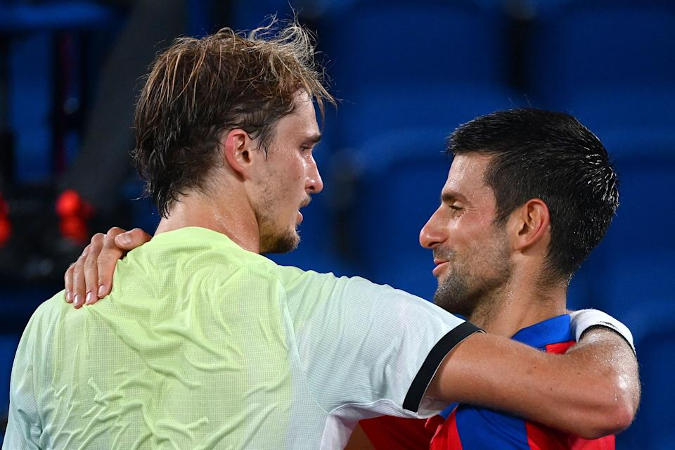 Serbia's Novak Djokovic (R) congratulates Germany's Alexander Zverev for winning their Tokyo 2020 Olympic Games men's singles semifinal tennis match at the Ariake Tennis Park in Tokyo on July 30, 2021. (Photo by Vincenzo PINTO / AFP) (Photo by VINCENZO PINTO/AFP via Getty Images)