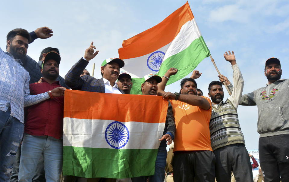 Indians hold national flags and shout slogan as they wait to welcome Indian pilot at India Pakistan border at Wagah, 28 kilometers (17.5 miles) from Amritsar, India, Friday, March 1, 2019. Pakistan is preparing to hand over a captured Indian pilot as shelling continued for a third night across the disputed Kashmir border even as the two nuclear-armed neighbors seek to defuse the most serious confrontation in two decades. (AP Photo/Prabhjot Gill)